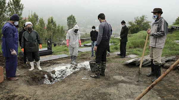 People wearing protective clothing, masks and gloves, pray during the funeral of a victim who died from the new coronavirus