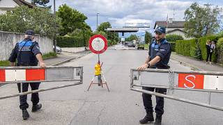 Two border guards opens the barrier that closed access to customs, in Thonex near Geneva, Switzerland, on Sunday, June 14, 2020.