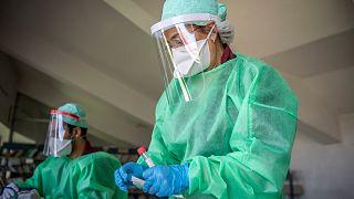 عاملة في القطاع الصحي تجمع عينات من مواطنين لاختبار كورونا