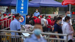 Des agents de sécurité regardent les travailleurs faire la queue devant un bâtiment proche d'un marché qui a été fermé à Pékin, le 12 06 2020
