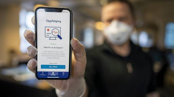 A man holds a mobile phone showing Norway's National Institute of Public Health new mobile app infection stop for infection tracking, in Oslo, Norway, Friday April 17, 2020