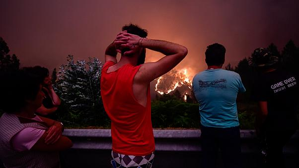 Villagers stare at the flames in despair during the 2017 deadly wildfire near Pedrógão Grande, Portugal