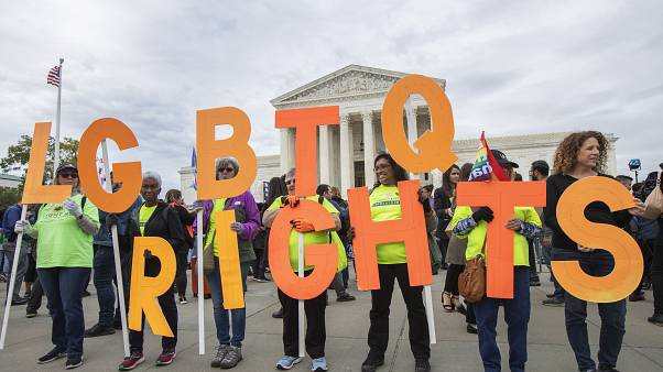 FILE - In this Oct. 8, 2019, file photo, supporters of LGBTQ rights hold placards in front of the U.S. Supreme Court in Washington.