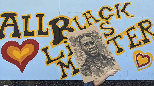 متظاهر يحمل صورة لجورج فلويد في ولاية كاليفورنيا