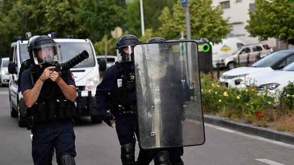 Police walk carrying a shield and a tear gas canister launcher in the Gresilles area of Dijon, eastern France, on June 15, 2020.