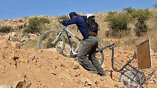 Wilfredo Negrete empuja su bicicleta mientras de dirige a dar clase a sus alumnos confinados