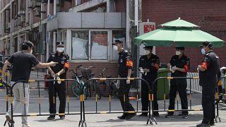 Des gardes de la sécurité à l'entrée d'un quartier bouclé de Pékin, le 16 juin 2020