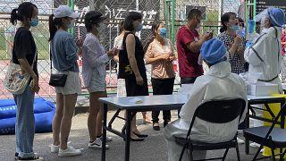 Koronavírus-tesztelésre várakoznak egy karantén alá vont negyed lakosai egy pekingi sportközpontban