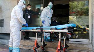 Διασώστες φορώντας προστατευτικές στολές και στέλεχος της Πολιτικής Προστασίας ετοιμάζονται να μεταφέρουν ασθενείς από την ιδιωτική κλινική Ταξιάρχαι,