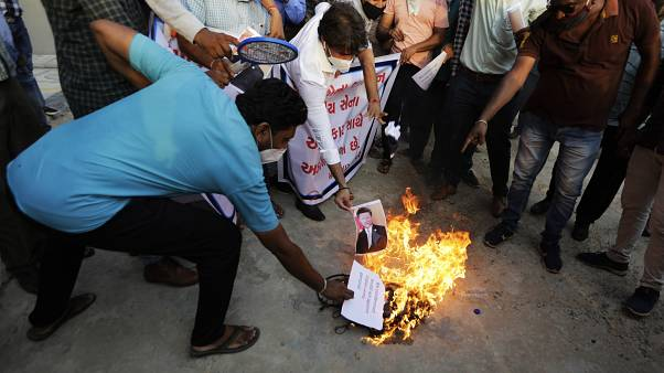 An Indian man burns a photograph of Chinese president Xi Jinping during a protest against China in Ahmedabad, India, Tuesday, June 16, 2020.