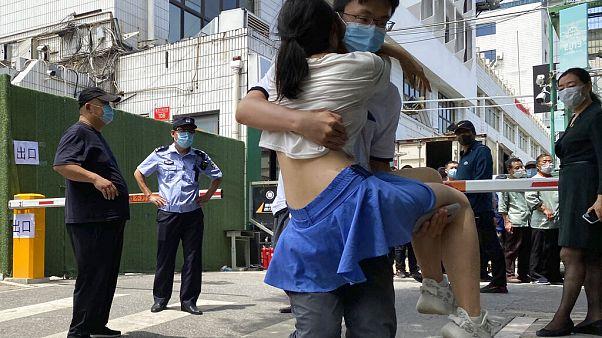 Una mujer es sacada en brazos de un centro de tests en Pekín