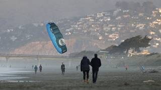 A windsurfer reels in his kite at New Brighton Beach in Christchurch, New Zealand, Tuesday, June 9, 2020.