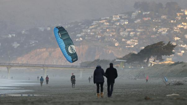 A windsurfer reels in his kite at New Brighton Beach in Christchurch New Zealand Tuesday