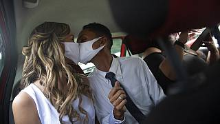 Wearing masks to prevent the spread of the coronavirus, a couple kiss during their drive-thru wedding in Brazil.