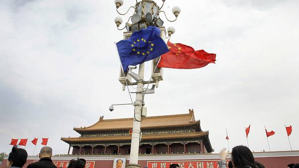 Visitors walk under flags of European Union and China in front of The Tiananmen Gate in Beijing Friday, April 25, 2008
