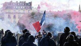 Protesters with a French flag face police during clashes on the Invalides esplanade at a demonstration in Paris. 16 June 2020
