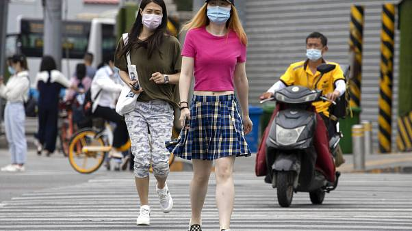 Residents wearing masks to curb the spread of the coronavirus cross the street in Beijing on Wednesday, June 17, 2020.