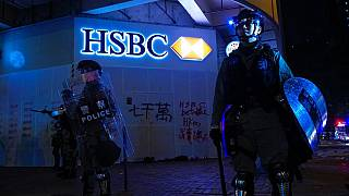 Police stand guard in front of a vandalized HSBC bank