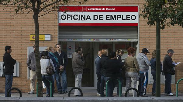 People queue outside an unemployment registry office in Madrid, Spain