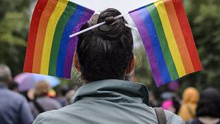A woman with rainbow colored flags in her hair waits for the start of a gay pride parade in Bucharest, Romania, Saturday, May 20, 2017.