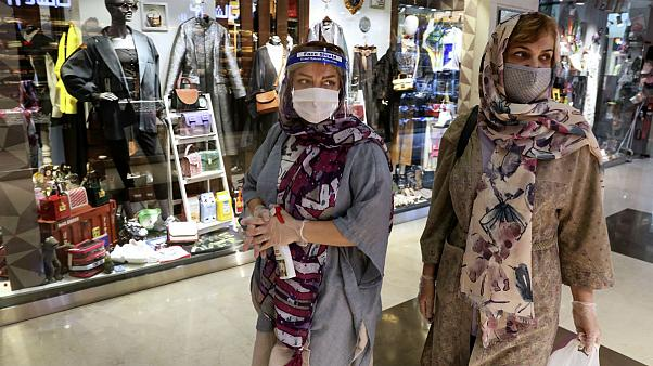 Women wearing protective face masks and gloves to help prevent the spread of the coronavirus shop at the Kourosh Shopping Center in Tehran, Iran