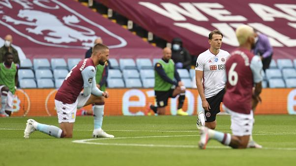 Players kneel prior to the start of the English Premier League soccer match between Aston Villa and Sheffield United at Villa Park in Birmingham, England, Wednesday, June 17,