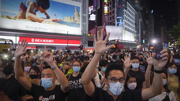 """Protesters singing and gesture with five fingers, signifying the """"Five demands - not one less"""" during a protest in Causeway Bay, Hong Kong, Friday, June 12, 2020."""