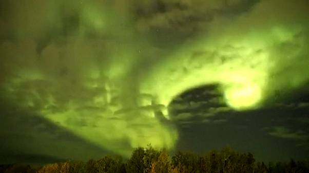 Wide shot thern lights shine through moving clouds