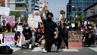 Des manifestants s'agenouillent dans un moment de silence devant le commissariat de Long Beach, le 31 mai 2020, lors d'une manifestation en mémoire à George Floyd.