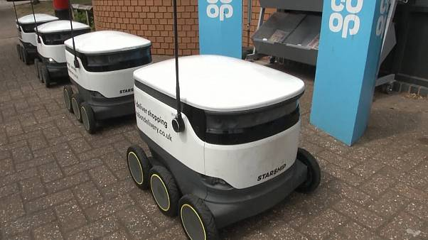 delivery robots lined up outside of grocery store