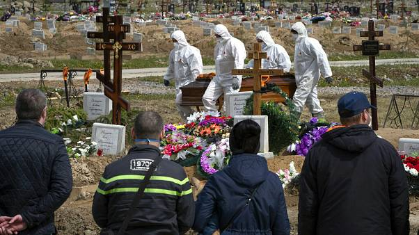 Gravediggers in protective suits carry the coffin of a COVID-19 victim