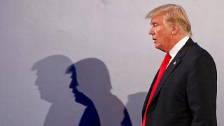 File - US President Donald Trump casts shadows on the wall after a press conference, in Warsaw, Poland, July 6, 2017