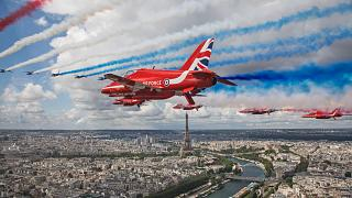 The Royal Air Force Aerobatic Team, the Red Arrows, and the French Air Force Aerobatic Team, La Patrouille de France, perform a fly-past over Paris, France