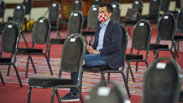 Egy horvát parlamenti képviselő várja az ülés kezdetét 2020 áprilisában.