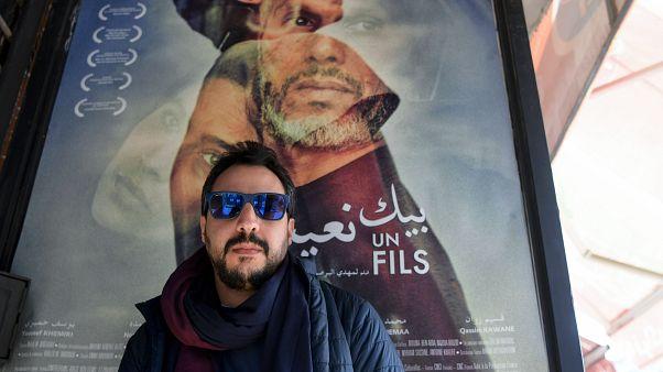 """معلقة إشهارية للفيلم التونسي """"بيك نعيش"""" يقف أمامها المخرج مهدي البرصاوي"""