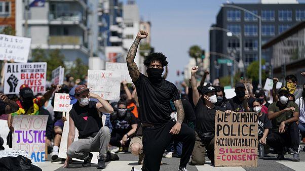 manifestantes se arrodillan en silencio frente a la comisaría de Long Beach el 31 de mayo de 2020, durante una manifestación en memoria de George Floyd.