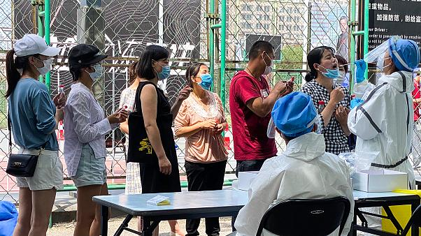 Residents line up to get tested at a coronavirus testing center set up outside a sports facility in Beijing. 16 June 2020
