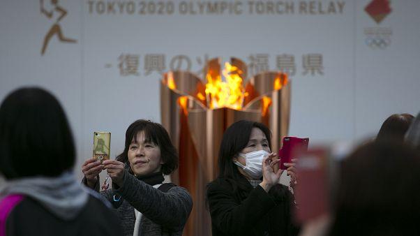 En esta foto de archivo del 24 de marzo de 2020, la gente se toma fotos con la Llama Olímpica durante una ceremonia en la ciudad de Fukushima, Japón.