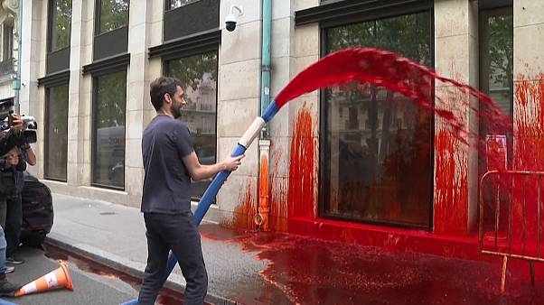 Mid shot activist spraying the Medef headquarters facade with fake blood