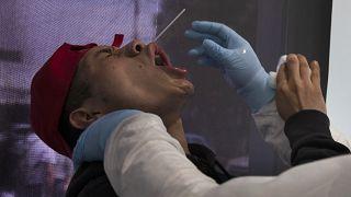عامل من القطاع الصحي يحاول أخذ عينة للاختبار من عامل في أحد أسواق مدينة مكسيكو