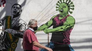 A man, wearing a protective face mask as a measure to curb the spread of the new coronavirus, walks past a mural in Sao Paulo, Brazi, June 19, 2020