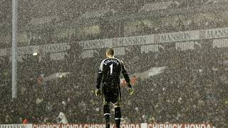 Tottenham Hotspur's goalkeeper Paul Robinson stands alone in the pouring rain during a Premier League match against Liverpool in 2006.