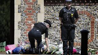 A Police officer places flowers from a woman at the scene of a fatal multiple stabbing attack in Forbury Gardens, central Reading, England, Monday June 22, 2020.