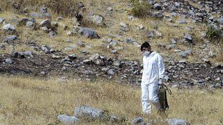عنصر من طاقم جنائي في موقع مقبرة جماعية في المكسيك
