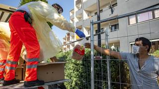 Red Cross helpers wear face masks and protective clothing while distributing bread to residents of a house that has been quarantined in Verl, Germany, Sunday, June 21, 2020.