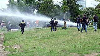 Police use a water cannon during a demonstration targeting the government's handling of the coronavirus crisis, in Malieveld, the Hague, Netherlands, Sunday, June 21, 2020.