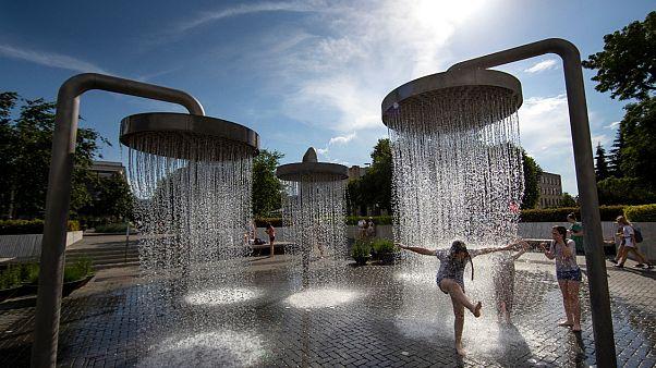 أطفال يمرحون تحت مياه نافورة في إحدى ساحات العاصمة الليتوانية فيلينوس في ظل ارتفاع درجات الحرارة -2020/06/19