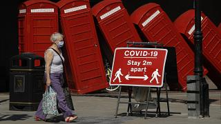 """A sign requesting people stay two metres apart to try to reduce the spread of COVID-19 is displayed in front of """"Out of Order"""" a 1989 red phone box sculpture"""