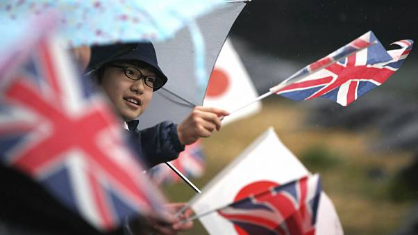 A student waves flags of Britain and Japan
