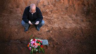 A Libyan man prays for a relative, one of many discovered in a mass grave,